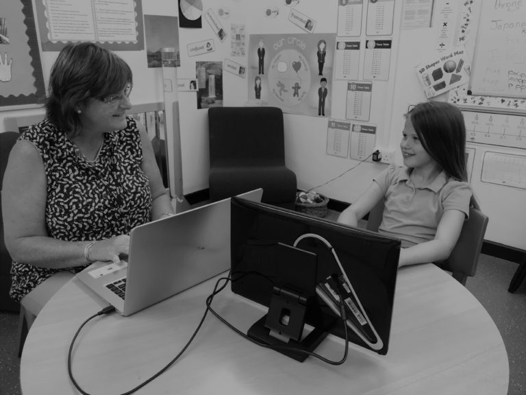 Photograph of teacher and pupil completing Lexplore onscreen reading assessment